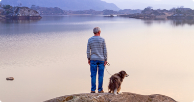 Pensive man and his dog looking across beautiful water scenery.