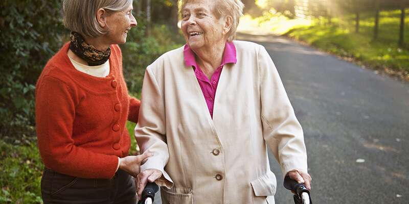 An older woman helps another older woman outside with her walker.
